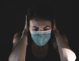 Koronawirus. Kobieta w masce ręce za głową