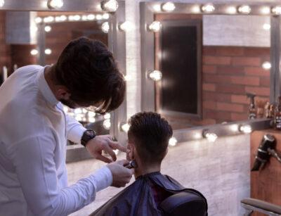 Zakład fryzjerski. Fryzjer strzyże klienta. Kara sanepidu